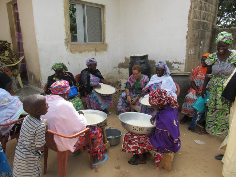 Senegalese ladies preparing meal at baby naming ceremony